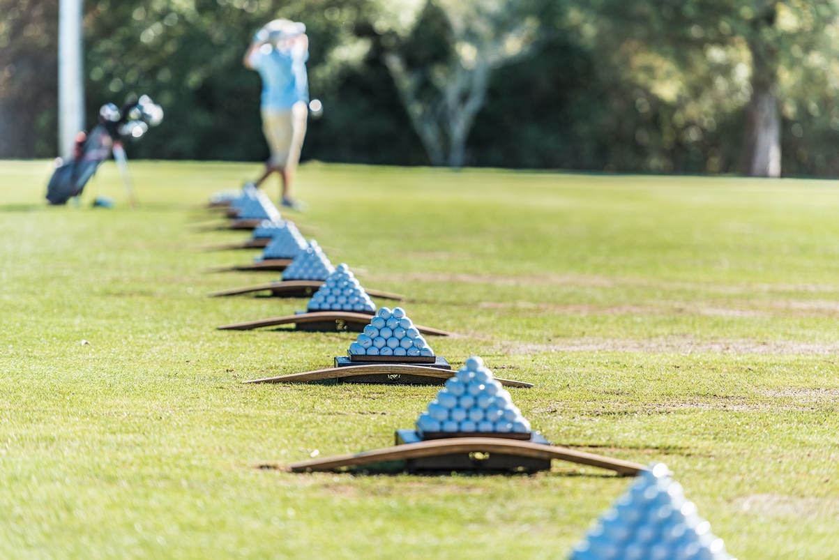 A line of golf balls are prepared for use at a driving range